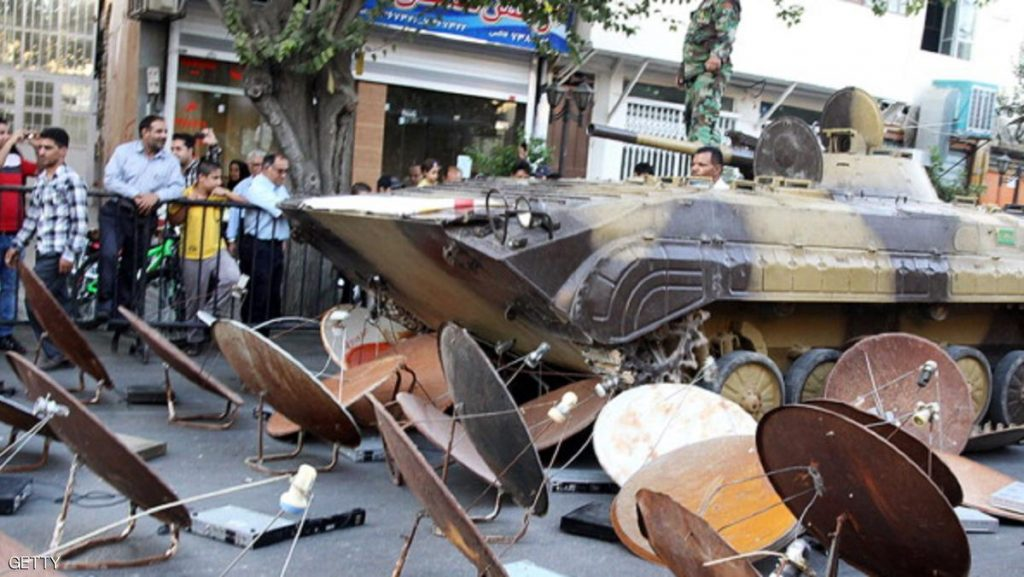 A picture taken on September 28, 2013 and obtained from Iran's ISNA news agency shows Iranian soldiers destroying satellite dishes with an army tank in a street of the southwestern city of Shiraz. The Iranian authorities carry out regular crackdowns to seize satellite dishes, removing them from rooftops, and issue warnings against their use. AFP PHOTO/ ISNA/MOHSEN TAVARO (Photo credit should read MOHSEN TAVARO/AFP/Getty Images)