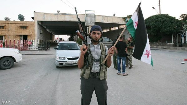 A Free Syrian Army soldier poses holding a rifle and a Syrian flag at the Bab al-Salama border crossing to Turkey on July 22, 2012. Anatolia reported that rebel fighters took Al-Salam on July 22 after hours of fighting during the night, and that the sounds of the battle could be heard from the Turkish side of the border. Syrian rebels are now in control of the Jarabulus, Bab al-Hawa and Al-Salam posts along the nearly 900-kilometre (560-mile) frontier with Turkey, a Turkish diplomat and Anatolia said. AFP PHOTO/ ADEM ALTAN        (Photo credit should read ADEM ALTAN/AFP/Getty Images)
