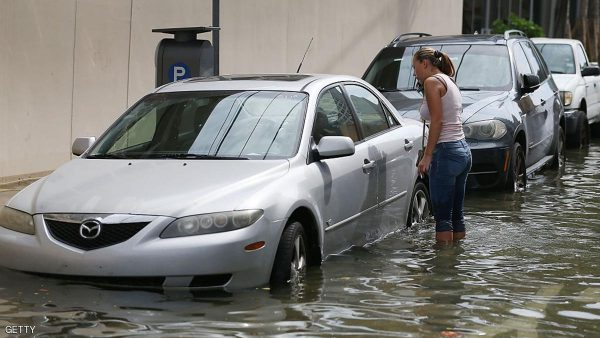 MIAMI BEACH, FL - SEPTEMBER 29:  Yana Kibyakova looks at her car parked along a flooded street that was caused by the combination of the lunar orbit which caused seasonal high tides and what many believe is the rising sea levels due to climate change on September 29, 2015 in Miami Beach, Florida. The City of Miami Beach is in the middle of a five-year, $400 million storm water pump program and other projects that city officials hope will keep the ocean waters from inundating the city as the oceans rise even more in the future.  (Photo by Joe Raedle/Getty Images)