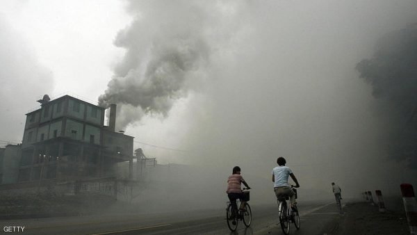 "Yutian, CHINA: TO GO WITH AFP STORY : TOOLBOX FOR FIXING CLIMATE CHANGE WITHIN REACH... (FILES) This picture taken 18 July 2006 shows cyclists passing through thick pollution from a factory in Yutian, 100km east of Beijing in China's northwest Hebei province. The UN's Intergovernmental Panel on Climate Change (IPCC) ""summary for policymakers"" on how to mitigate climate change is to be issued in Bangkok next 04 May after a five-day meeting.   AFP PHOTO/Peter PARKS/FILES (Photo credit should read PETER PARKS/AFP/Getty Images)"