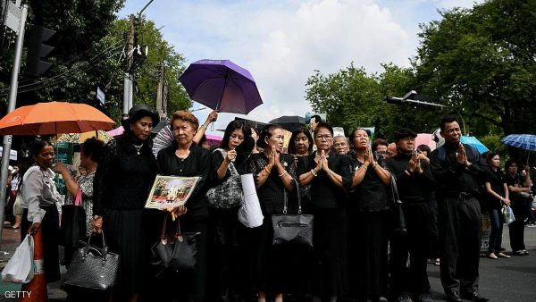 Mourners wearing black clothes hold portraits of the late Thai King Bhumibol Adulyadej as they wait to pay their respects outside the Grand Palace in Bangkok on October 15, 2016. Thailand's government has warned of a national shortage of black clothing, which is flying off shelves as a distraught nation mourns beloved late King Bhumibol Adulyadej. / AFP / MANAN VATSYAYANA        (Photo credit should read MANAN VATSYAYANA/AFP/Getty Images)